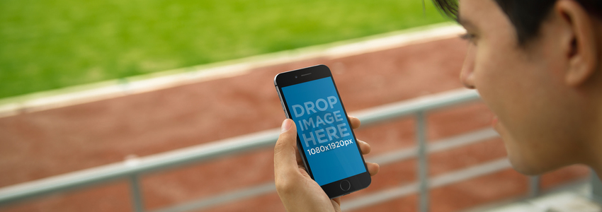 Mockup of a Young Man Using iPhone 6 at a Running Track a3836