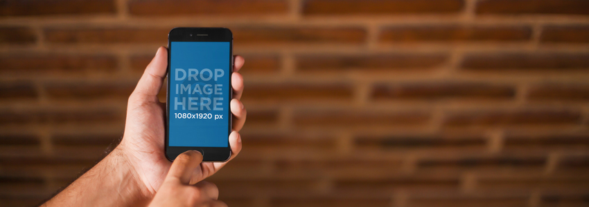 iPhone 6 Mockup of a Man Holding his iPhone in Front of a Brick Wall