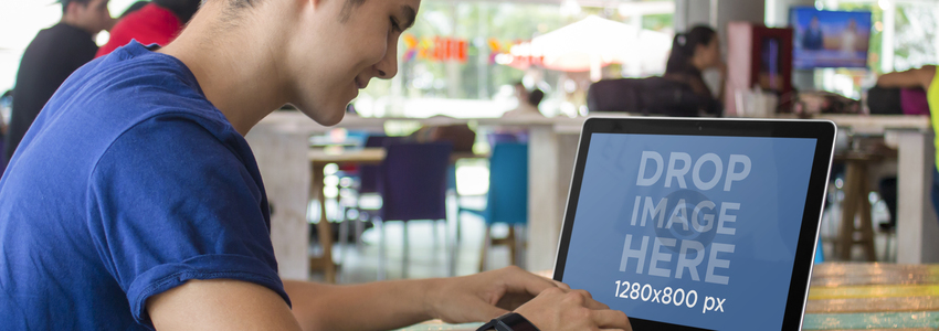 Mockup of a Young Man Working on his Macbook Pro at a Restaurant a4641