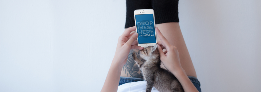 iPhone Mockup of a Tattooed Girl on a Bed with her Kitten a12804wide