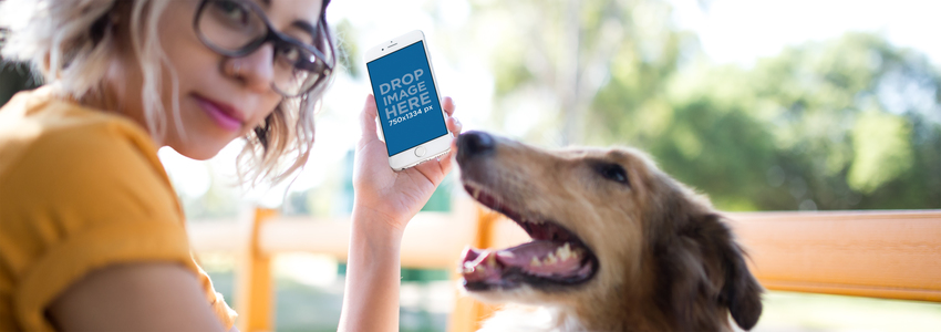 Young Trendy Girl Holding an iPhone 6 Mockup in Vertical Position with her Dog Outdoors a12794