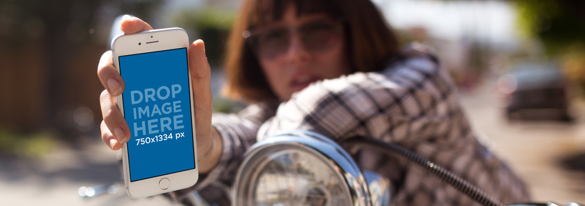 iPhone 7 Mockup Held in Portrait Position by a Girl with a Plaid Shirt and Short Hair on a Motorcycle a12955wide