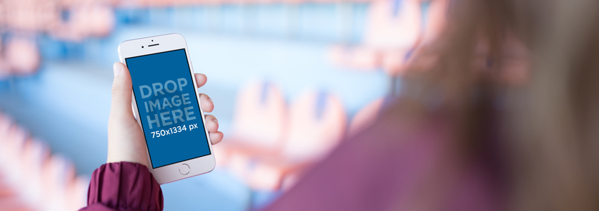 Mockup Of A Girl Using Her White iPhone 6 While At A Red And Blue Stadium a14091wide