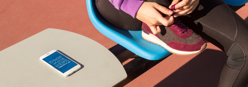 Mockup Of A White iPhone 6 Lying Over A Table While A Girl Is Tying Her Laces In A Plastic Chair a14094wide