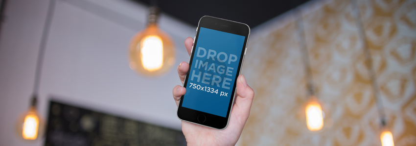iPhone Being Held By A Womans Hand Inside A Room With Hanging Lamps Mockup a14006wide